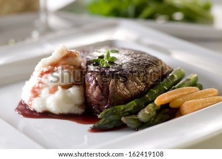Closeup of a gourmet dinner plate with a rare and juicy tenderloin steak, asparagus, carrots, mashed potatoes and a port wine reduction.