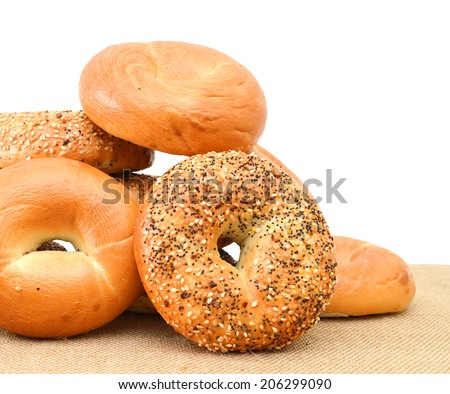 Closeup of a group of assorted bagels on a wood table top with burlap in the background  - stock photo