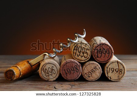 Closeup of a group of wine corks and a corkscrew on a rustic wood table and a light to dark warm background. - stock photo