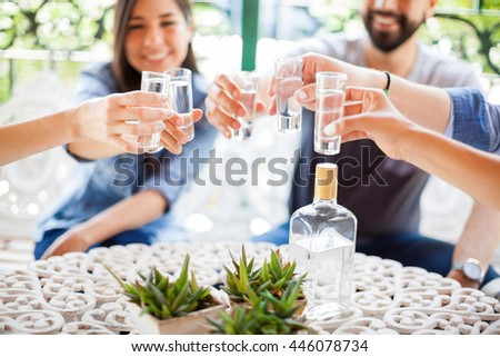 Closeup of a group of young Hispanic friends having fun together and drinking shots of tequila during a barbecue - stock photo