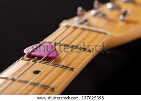 Closeup of a guitar neck with pink pick - stock photo
