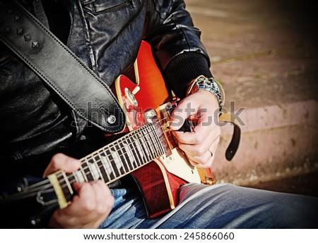 closeup of a guitar player with electric guitar - stock photo