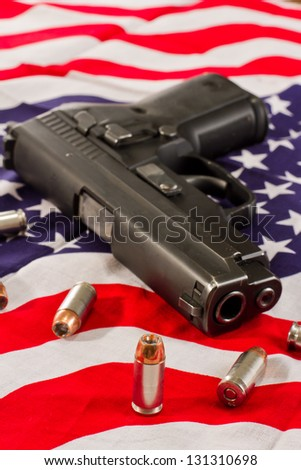 closeup of a hallow point bullet with a gun and an American flag fading to a shallow depth of field - stock photo