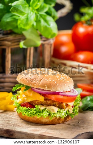 Closeup of a hamburger with chicken and fresh vegetables