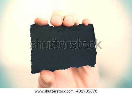 Closeup of a hand gripping blank crafted business card with uneven edges on yellow background. Mock up - stock photo