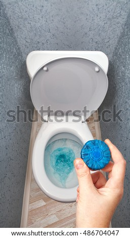Closeup of a hand holding a blue toilet cleaner tablets for the toilet tank against a white, ceramic toilet bowl.
