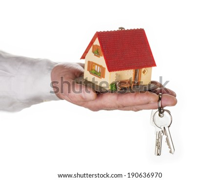 Closeup of a hand holding a model house and a key.
