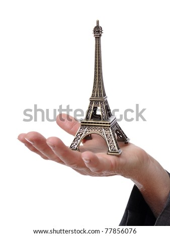 Closeup of a hand showing a tiny Eiffel Tower isolated on white background - stock photo