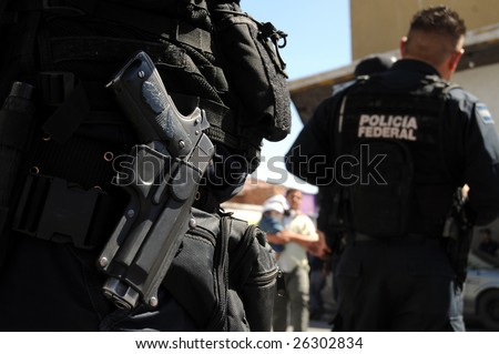 Closeup of a handgun of Mexican federal police forces maintaining order in the violent border city of Ciudad Juarez - stock photo