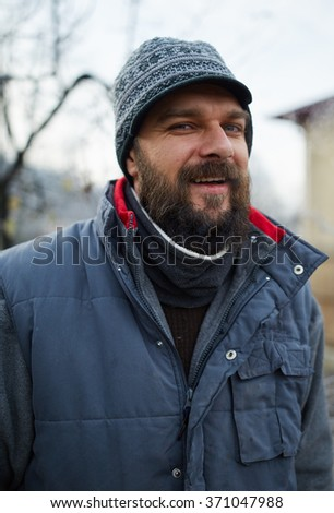 Closeup of a handsome bearded young farmer in the countryside