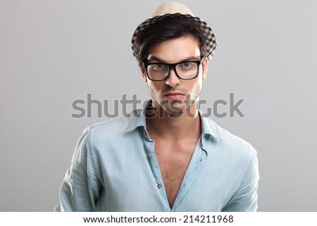 Closeup of a handsome man in blue shirt, glasses, looking at the camera