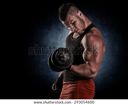 Closeup of a handsome power athletic man bodybuilder doing exercises with dumbbell - stock photo
