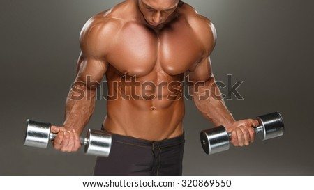 Closeup of a handsome power athletic man bodybuilder doing exercises with dumbbell. Fitness muscular body on dark background. - stock photo