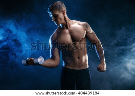 Closeup of a handsome power athletic man bodybuilder doing exercises with dumbbell. Fitness muscular body on dark  smoke background. Perfect male. Awesome bodybuilder, tattoo, posing.  - stock photo