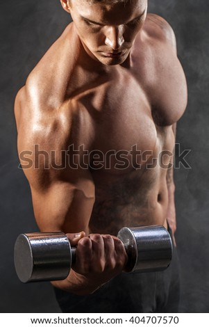 Closeup of a handsome power athletic man bodybuilder doing exercises with dumbbell. Fitness muscular body on dark background. Selective Focus. Awesome bodybuilder, tattoo, posing.  - stock photo