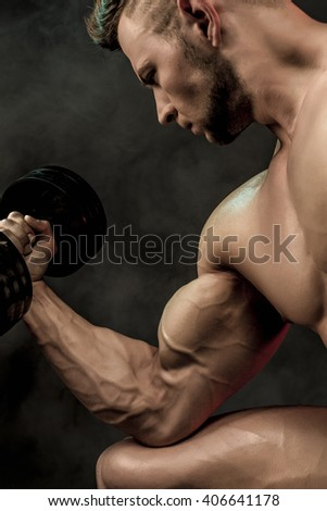 Closeup of a handsome power athletic man bodybuilder doing exercises with dumbbell. Fitness muscular body on dark background. Selective Focus. Awesome bodybuilder, posing.