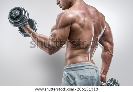 Closeup of a handsome power athletic man bodybuilder doing exercises with dumbbells. Fitness muscular body on white background. - stock photo
