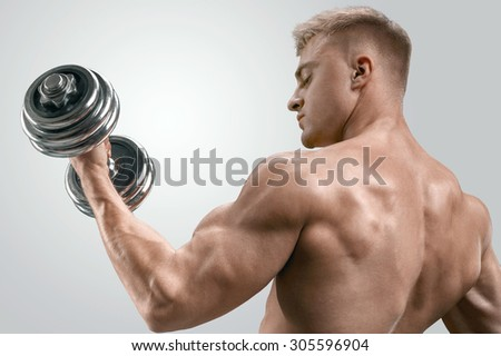 Closeup of a handsome shirtless athletic man doing exercises with dumbbell. Muscular bodybuilder on white background. - stock photo