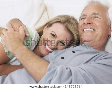 Closeup of a happy middle aged couple embracing in bed - stock photo