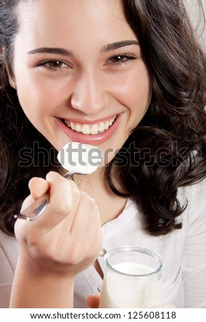 Closeup of a happy woman laughing while eating a yogurt. Looking at the camera. - stock photo