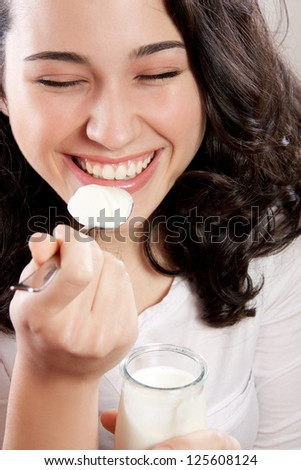 Closeup of a happy woman laughing with eyes closed while eating a yogurt. - stock photo