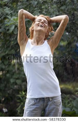 Closeup of a happy young woman enjoying rain - stock photo