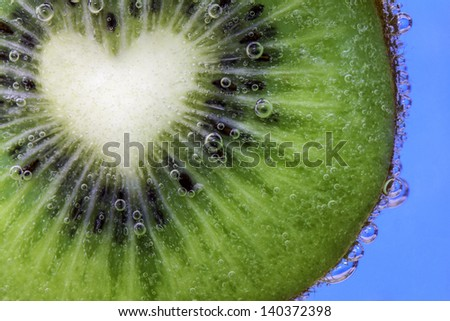 Closeup of a heart shaped kiwi slice covered in water bubbles - stock photo