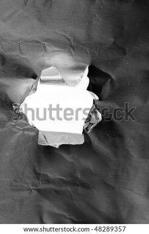 closeup of a hole torn in a piece of metal - stock photo