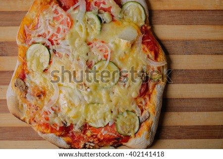 closeup of a homemade pizza on wooden background
