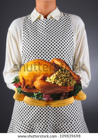 Closeup of a homemaker in an apron and oven mitts holding a platter with a roasted Thanksgiving turkey. Horizontal format over a light to dark background. Woman is unrecognizable. - stock photo