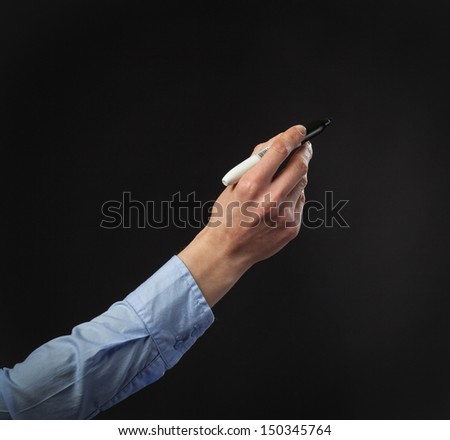 Closeup of a human hand writing with marker on dark background; copy space
