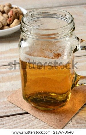 Closeup of a jar mug with beer. Vertical format on a rustic wood table and peanuts in the background. - stock photo