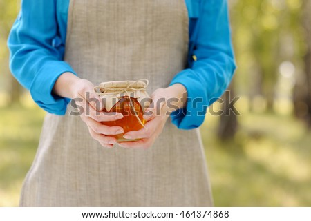 Closeup of a jar of honey in the hands of women