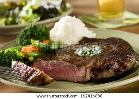Closeup of a juicy ribeye steak with vegetables and mashed potatoes.