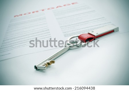 closeup of a key and a mortgage loan contract - stock photo