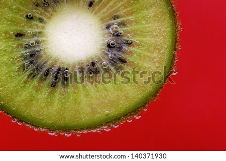 Closeup of a kiwi slice covered in water bubbles against a red background - stock photo