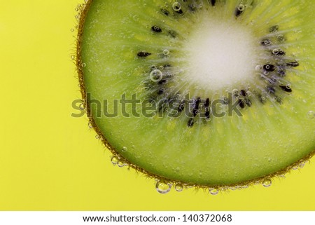 Closeup of a kiwi slice covered in water bubbles against a yellow background - stock photo