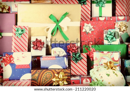 Closeup of a large stack of wrapped Christmas presents of varying sizes and shapes  - stock photo