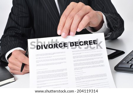 closeup of a lawyer sitting in his desk showing a divorce decree - stock photo
