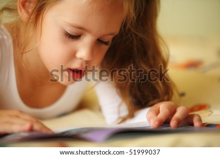 closeup of a little girl lying reading a book on her bed - stock photo