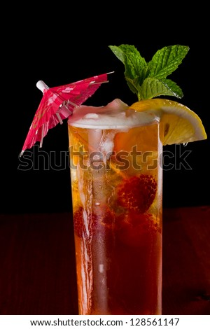 closeup of a long island red tea served on a dark bar top garnish with a lemon