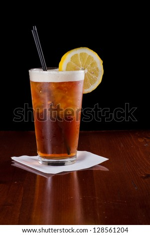 closeup of a long island red tea served on a dark bar top garnish with a lemon isolated on black - stock photo