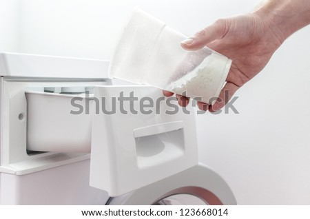 Closeup of a male hand filling detergent into the drawer of a washing machine. - stock photo