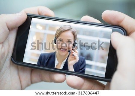 Closeup of a male hand holding a smart phone during a skype video