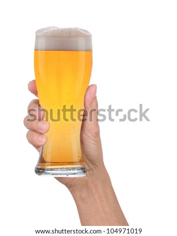 Closeup of a male hand holding up a glass of beer over a white background. Vertical format with condensation side of the beer glass.
