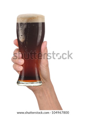 Closeup of a male hand holding up a glass of foamy dark ale over a white background. Vertical format with drip running down the side of the beer glass. - stock photo