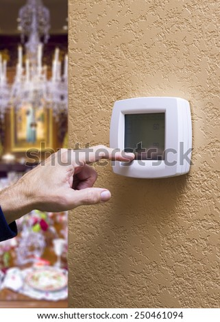 Closeup of a male hand pressing a button on a digital thermostat - stock photo