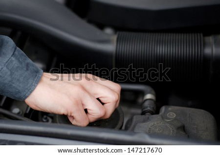 Closeup of a male mechanic's hand working on car motor