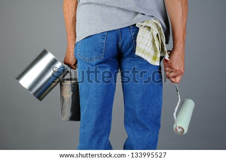 Closeup of a male painter seen from behind while he carries two paint cans and a roller. Man is unrecognizable, torso and legs only. Horizontal format.
