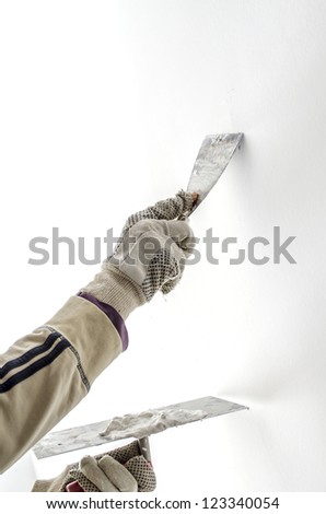 Closeup of a man aligning a wall with spatula and trowel.